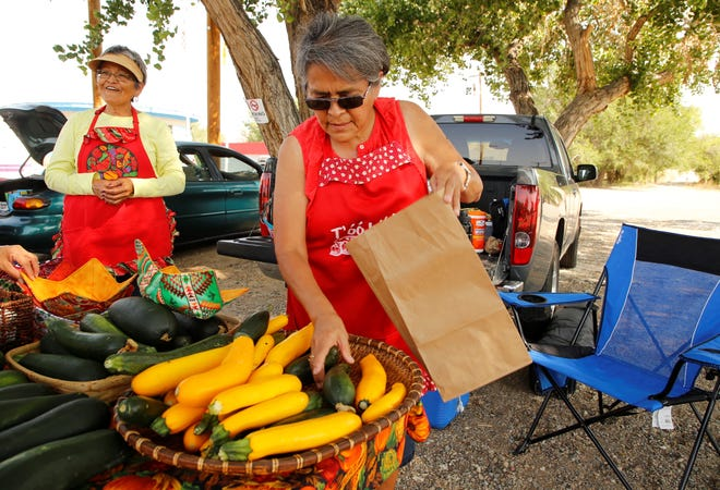 Evangie Begay, left, visits with a customer while her sister, Cheryle Benally, bags zucchini and yellow squash at the Shiprock Farmers' Market on July 10 at the Shiprock Chapter house parking lot.