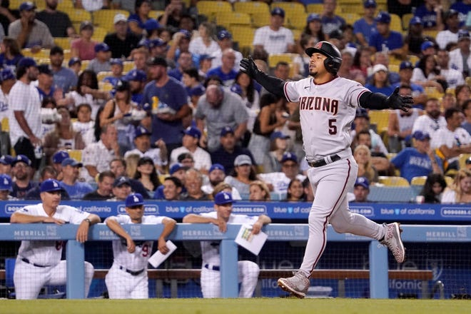 Arizona Diamondbacks' Eduardo Escobar gestures before scoring on a two-run home run while members of the Los Angeles Dodgers watch from the dugout during the fifth inning of a baseball game Friday, July 9, 2021, in Los Angeles. (AP Photo/Mark J. Terrill)