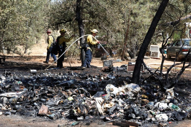 Firefighters extinguish a 3-acre vegetation fire that also burned trash at a homeless encampment near Twin View Boulevard and Crooked Oak Lane in north Redding on Friday afternoon, July 9, 2021. Fire officials say the fire's cause was still under investigation.