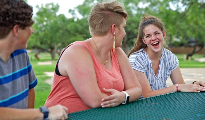 Destany Ellis-Dearborn, far right, shares a laugh with her parents Kristin Ellis-Dearborn, far left, and Stephanie Ellis-Dearborn, center, at Unidad Park on Friday, July 9, 2021.