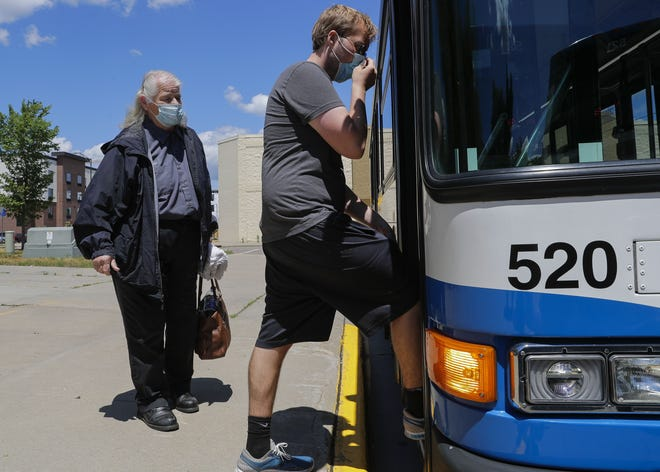 City bus driver Bobbie Marvin (left) and Cody Kapitzke board their bus June 22 at the transfer station in downtown Stevens Point.