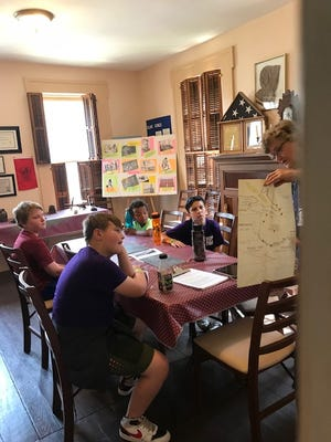 Children from Alliance YMCA Day Camp learn about the history of Haines House, which served as a stop on the Underground Railroad.