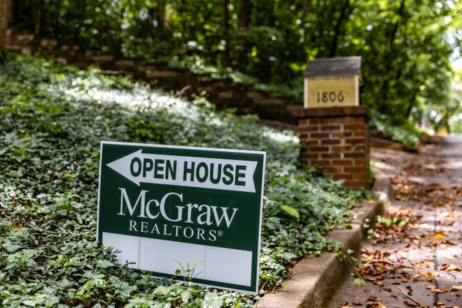 An open house sign sits outside a home for sale.