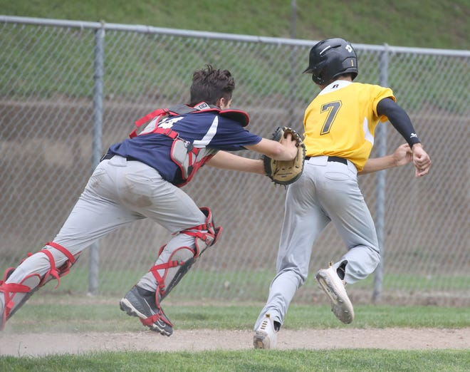 BTC Bank catcher Clayton Schuster applies the tag on KWRT's Edrissa Bah during a run down Wednesday night in Junior Babe Ruth action at Twillman field in Harley park. KWRT won 7-6.