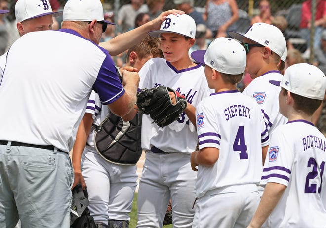 Blissfield Little League starting pitcher Jackson Jordan, center, is congratulated by his coaches and teammates after striking out the side early in Saturday's 10-11-12 District 16 title game against Plymouth Canton at Mitchell Park