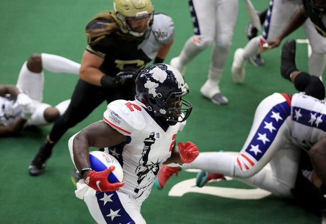 Salina Liberty running back Tracy Brooks (2) carries the ball with Dodge City's Jayden Dobbs (7) in pursuit during their Champions Indoor Football playoff game last Saturday at Tony's Pizza Event Center. Brooks ran for 77 yards and two touchdowns in the Liberty's 55-31 victory.