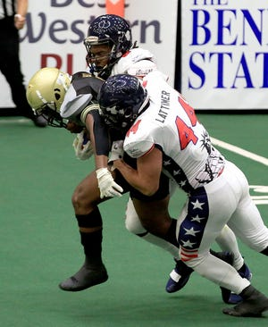 Salina Liberty defensive ends Travis Taylor (8) and Jake Lattimer (44) tackle Dodge City's Cameron Booty (5) during last week's game at Tony's Pizza Event Center. The Liberty play host to Omaha at 6:35 p.m. Saturday in Champions Bowl Vi.
