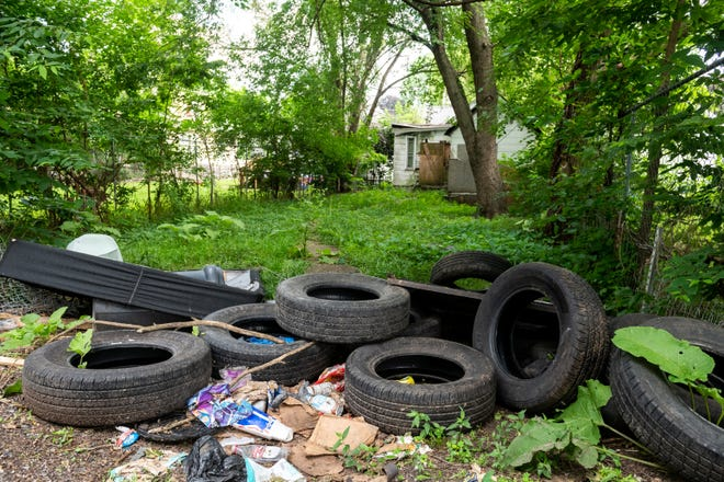 Used, abandoned tires lie in an alley behind an abandoned house in Peoria's south side on Wednesday, July 7, 2021. Used tires are often discarded on empty or abandoned lots.