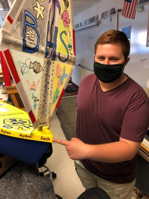 Burrillville High School student Zach Velleca stands alongside a small person-less sailboat that he and his classmates built from a kit. The boat was launched at an offshore canyon and it's headed for the Bay of Fundy in Canada following Tropical Storm Elsa.