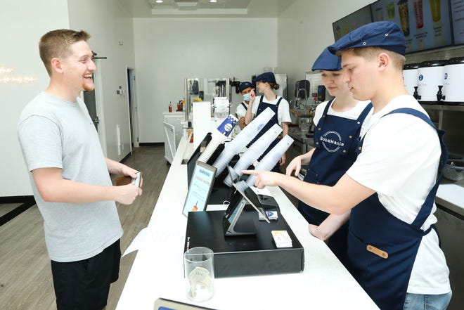 Jonathan Williamson becomes the first customer on a soft opening at BobaMania bubble tea house on University Boulevard in Tuscaloosa Saturday July 10, 2021. Store manager Shannon Grady and employee Joshua Harrelson take his order. [Staff Photo/Gary Cosby Jr.]