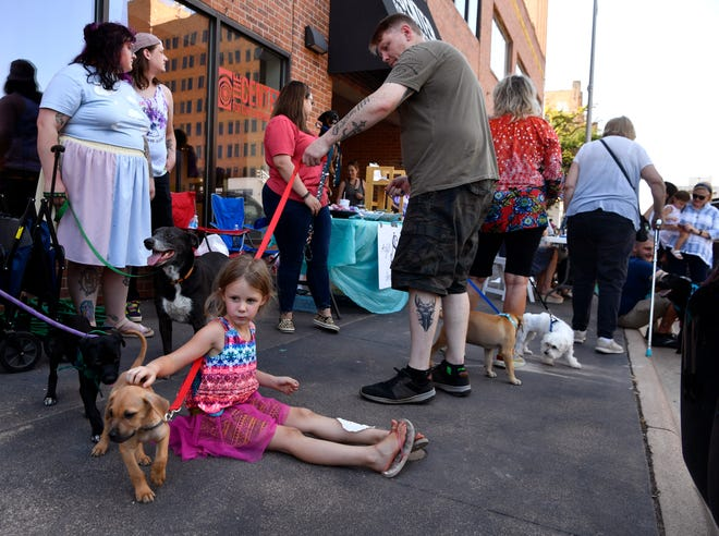 Young and old make friends with puppies available for adoption during Thursday's DogWalk on Cypress Street.