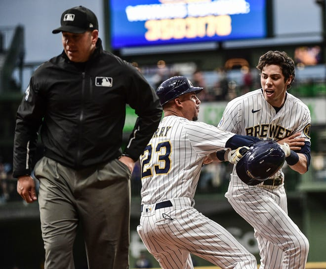 Brewers leftfielder Christian Yelich is restrained by first base coach Quintin Berry after being called out by first base umpire John Libka in the sixth inning during the game against the Cincinnati Reds at American Family Field on Saturday night.