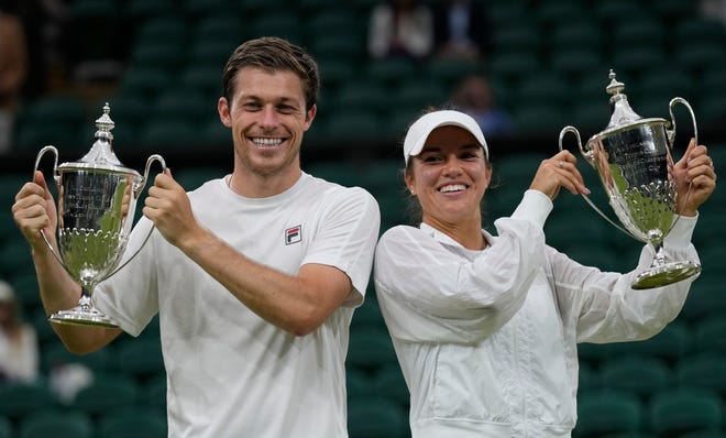 Desirae Krawczyk, right, of Rancho Mirage, and playing partner Neal Skupski of Great Britain celebrate with their trophies after they defeated Harriet Dart and Joe Salisbury in the mixed doubles final at the Wimbledon Tennis Championships in London on Sunday.