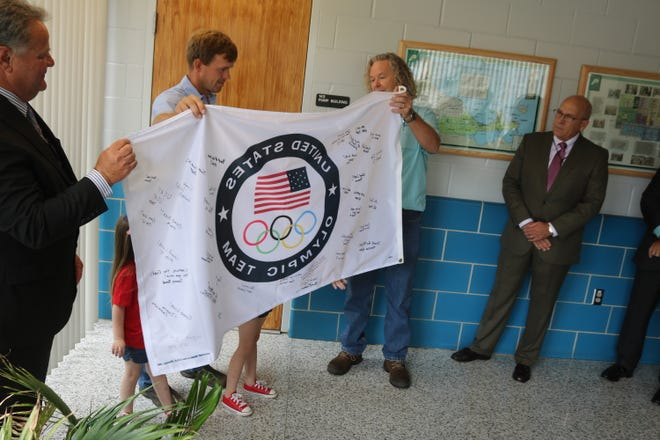 Jacob Wukie, center, holds an Olympic flag signed by his coworkers at the Ottawa County Regional Water Plant during a send-off celebration on July 9. The Olympic archer and Fremont resident is scheduled to compete Sunday night in Tokyo.