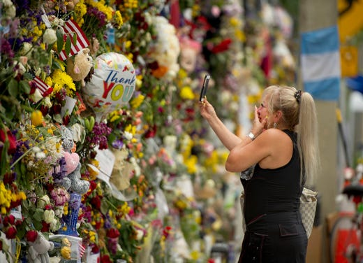 A woman is overcome with emotion while visiting the Surfside Wall of Hope and Memorial near the site of the Champlain Towers South building collapse in Surfside, Fla. June 10, 2021.