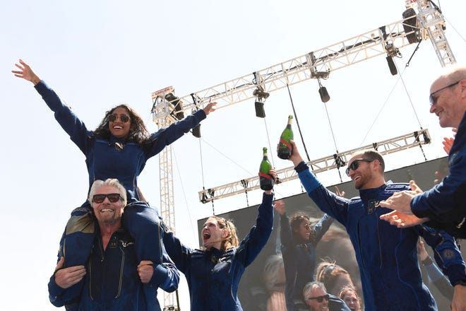 """Virgin Galactic founder Sir Richard Branson(L), with Sirisha Bandla on his shoulders, cheers with crew members after flying into space aboard a Virgin Galactic vessel, a voyage he described as the """"experience of a lifetime"""" — and one he hopes will usher in an era of space tourism."""
