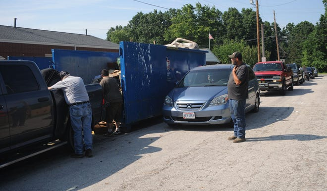 Vehicles wait in line to unload trash during the Lexington Township cleanup on June 26, 2021.