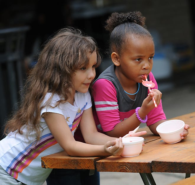 Calie Al-Aroud, 6, left, and Iyana Watson, 6, enjoy a cold treat during a free community picnic Saturday, July 10, 2021 at Silver Park.