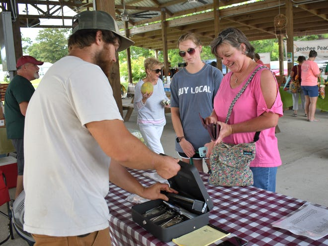 """Caroline Pope and her daughter Emily make a purchase from Boykin Ranch at the Market on Maple on July 8. Santa Claus is scheduled to be at the farmers market July 15 as part of the Screven County Chamber of Commerce's """"Christmas in July."""" Rather fittingly Emily Pope is wearing a T-shirt with """"Buy Local."""" Throughout Sylvania Thursday, businesses will offer specials to patrons in honor of the seven-month version of Dec. 25."""