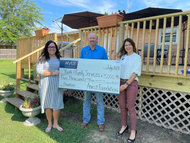 Arvest local bank president Kim Adams and commercial banker Chad Cox presented the check to Youth and Family Services executive director Katie Wilson.