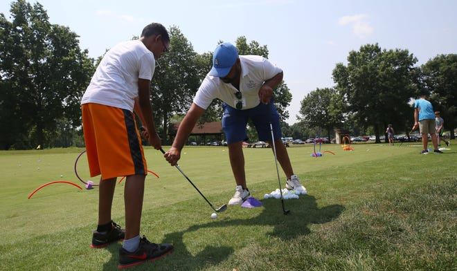 Brenden Woodfork, 13, of Reynoldsburg receives chipping pointers from First Tee of Central Ohio coach Ethan Pinckney on July 6 at Blacklick Woods. First Tee's mission is to teach young players life lessons in addition to golf.