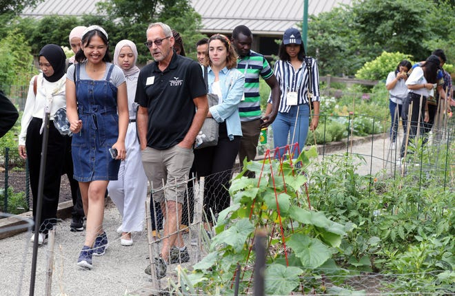Natasha Priyanti, an Ohio State University agriculture intern from Indonesia, laughs with Bill Dawson, Growing to Green project manager, as he leads a group of Ohio State interns through a tour of the Franklin Park Conservatory and Botanical Gardens' community gardens July 10. The organization helps individuals and groups in starting their own community gardens and neighborhood beautification projects.