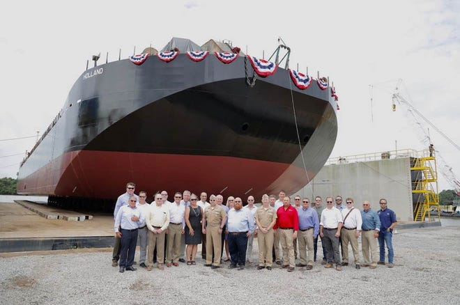 Representatives of the U.S. Navy, Bollinger Shipyards, General Dynamics Electric Boat and Bristol Harbor Group stand in front of the Holland. Bollinger, which built the ocean barge at its shipyard in Amelia, christened the vessel Saturday.