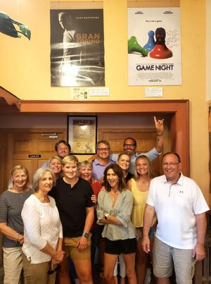 """Mark Perez, back right with arm raised, has his arm around Jeff Dufault and is pictured with other family at the Grand Theatre underneath the poster for the 2018 film he wrote, """"Game Night."""" Perez's wife, Valarie, is a Dufault cousin and is pictured in the center of the front row. Next to the 'Game Night' poster is the movie poster from the Clint Eastwood film, 'Gran Torino,' with the original story written by Dave Johannson, who grew up in Crookston."""
