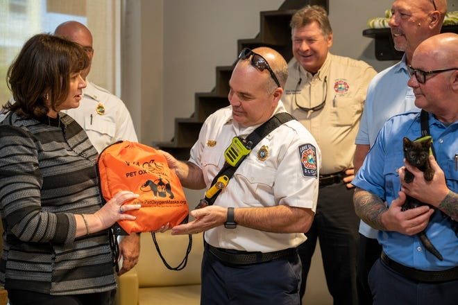 Sandra Cagan of The Orlando Cat Cafe in Clermont presents Ltn. Kirk Biccum of the Lake County Fire Rescue team with two pet oxygen masks on Monday  in honor of National Pet Fire Safety Day celebrated on July 15. [Cindy Peterson/Correspondent]
