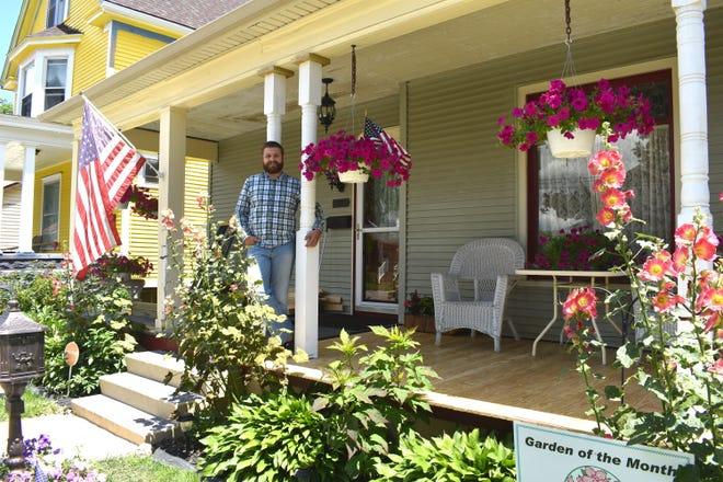 Vinny DiPonio stands on the front porch of his home at 124 Clinton St. in Adrian earlier this month. The Adrian Women's Garden Club selected DiPonio's home as its Garden of the Month for June.