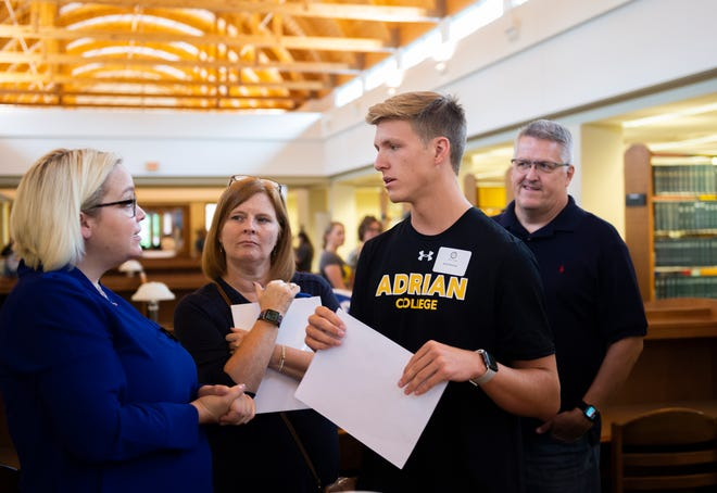 """Adrian College Assistant Dean of Academic Affairs Katie Rasmussen, left, speaks to incoming freshman Seth Parsons, third from left, of Toledo and his mother and father, Tanna and Chip Parsons, in Shipman Library during the college's """"Sneak Peek"""" event last week."""