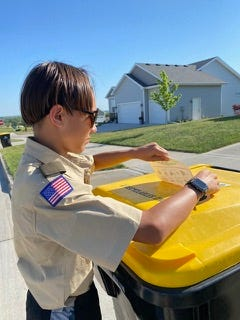 Adel Boy and Girl scouts are asking residents to leave their recycling bins out front for an extra day so that they can applyrecyclingstickers to the bins. Pictured is Boy Scout Paul Giles of Adel.
