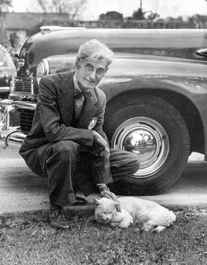 """Richard LeSesne pets a cat. He was the area's preeminent photographer of racing in the 1920s and 30s. """"Dean of local photographers,"""" The Daytona Beach Morning Journal called him in his obituary."""