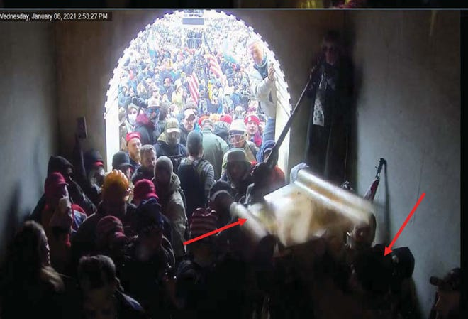 This image is from a 30-second video clip that St. Augustine resident John Anderson's attorney wants a court to clear for public release as Anderson awaits trial on charges from the Jan. 6 riot at the U.S. Capitol. Arrows on the image were placed by authorities to show a plastic police shield being passed through a crowd and over the head of a man prosecutors said was Anderson.