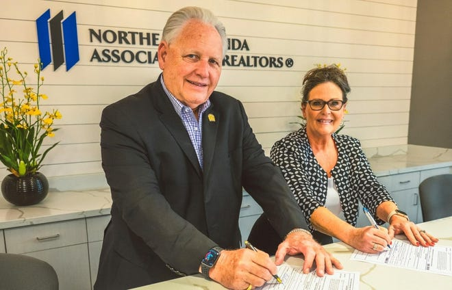 Northeast Florida Association of Realtors CEO William Glenn East (left) joins Missi Howell, NEFAR president, in signing the petition to place a constitutional amendment favoring affordable housing on the 2022 general election ballot.