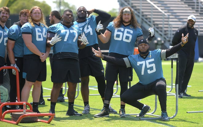 Members of the Jaguars offensive line mug for the photographers during the start of OTAs in May.