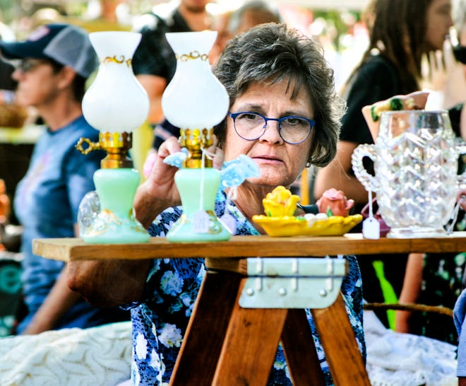 Janet Kruleski checks out antiques at one of the vendors' booths Saturday during the Finney County Historical Museum's annual Flea Market Festival.  Thirty vendors participated in this year's event, south of the museum in Lee Richardson Zoo.