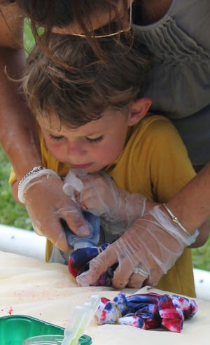 Beau Birkbeck gets an assist from his mother, Katelyn Birkbeck, at the Princeton Library tie dye program.