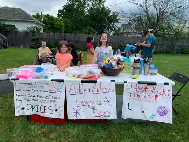 """Adeline Stump, 8, (left) and Aubrey Muniz, 9, (right) wanted to do a lemonade and Fidget Pack stand to learn how to be good entrepreneurs. Their grandparents, Nina and Bryan Smith, helped make that happen. They've been holding sales with signs on 4th and Monroe Street and their stand is on 4th across from Tim Horton's. The girls even hired their cousins to help, and paid them for their work. """"We want to show people that kids still do this kind of thing,"""" said Adeline's mother, Tabatha Champagne. """"By doing so, they are learning how to run a business, dealing with money and the value of hard work."""""""