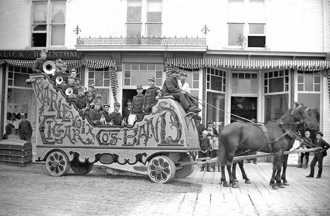 Master wagon maker David Nettleton's Charlevoix Cigar Company Band bandwagon in front of the Lewis Grand Opera House by the bridge, 1890s.
