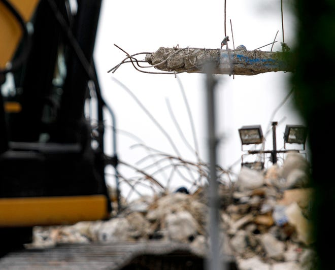 A section of rebar reinforced concrete is lifted from the remains of the Champlain Towers South condo in Surfside, Florida Monday, July 12, 2021.