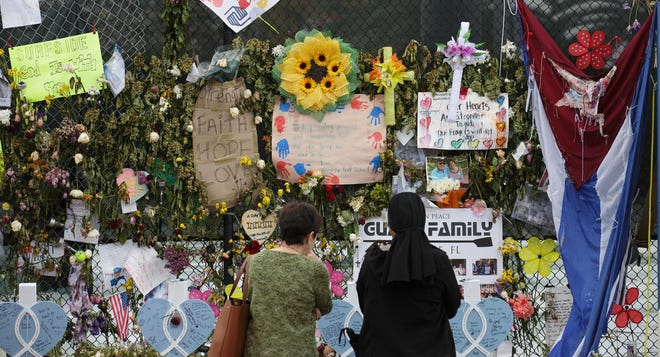 Women gaze at the items making up the memorial for the victims of the Champlain Towers South collapse in Surfside on July 12.