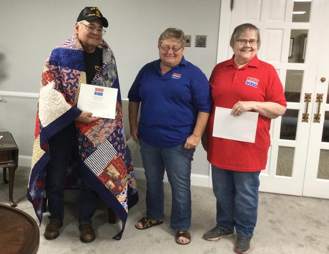 Debbie Withers (middle) and Rosalie Rose (right) present a local veteran with a Quilt of Valor in Pratt.