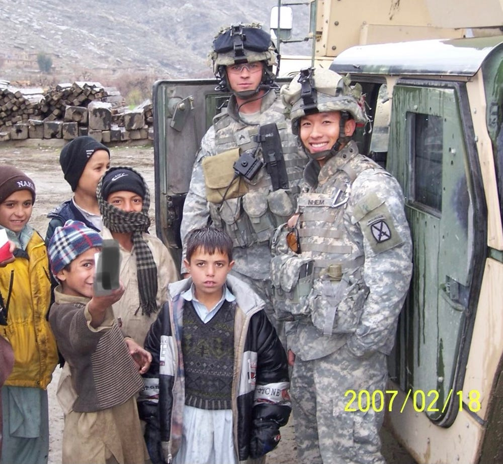 Nhem, at right, in Afghanistan's Korengal Valley in February 2007, often stopped on patrol to connect with local kids.