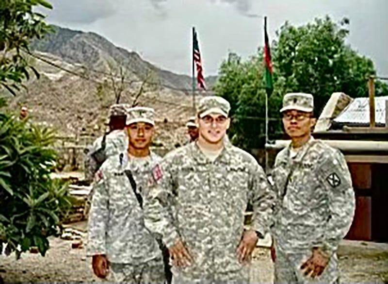 Nhem, left, with two fellow soldiers in Jalalabad Base in June 2006.