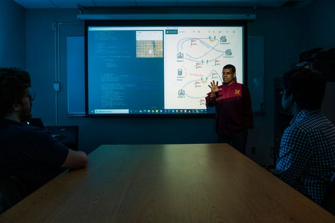 Dr. Sajal Das reviews work by Missouri S&T computer science graduate students on the Cyberinfrastructure for Accelerating Innovation in Network Dynamics project. Photo by Michael Pierce, Missouri S&T.