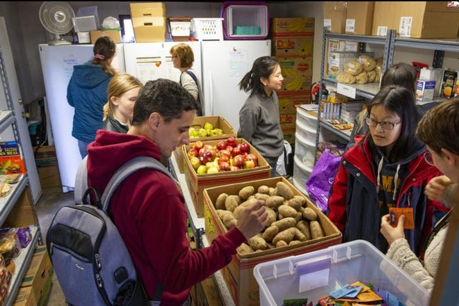 """University of Oregon students pick from food items in the student food pantry run by the Episcopal Campus Ministry run in partnership with FOOD for Lane County in 2019. The Legislature is paying for and requiring a """"benefits navigator"""" position to assist student in accessing things like food and housing."""