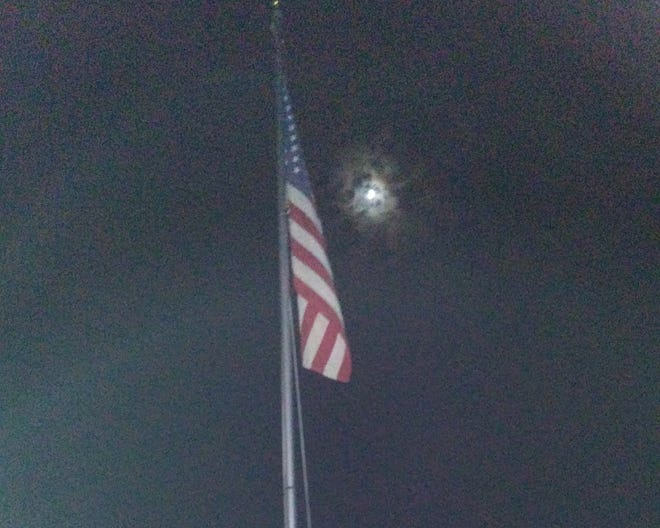 The moon sits over the American flag.