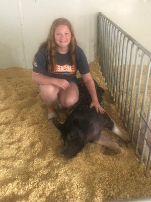 Hannah Tice poseswith one of her swine entries to the fair.