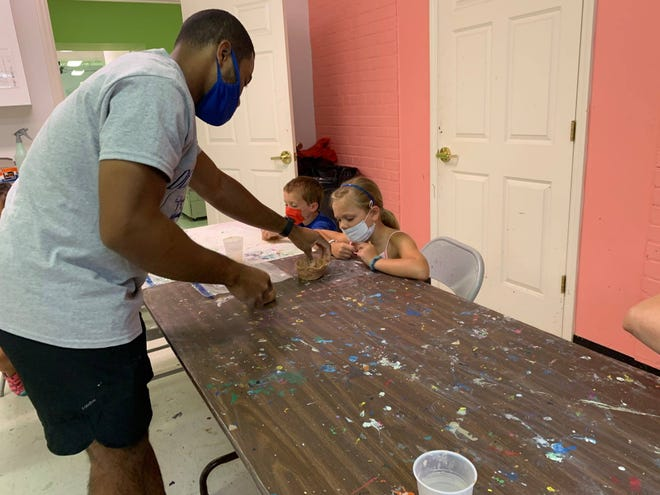 Crest High School Art Teacher CJ Norris helps a student form clay during a summer art course at the Cleveland County Arts Council.